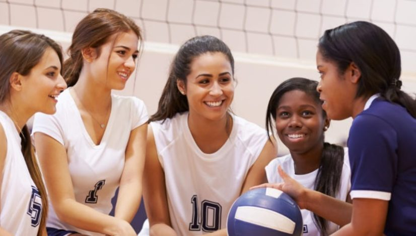 Female High School Volleyball Team Have Team Talk From Coach